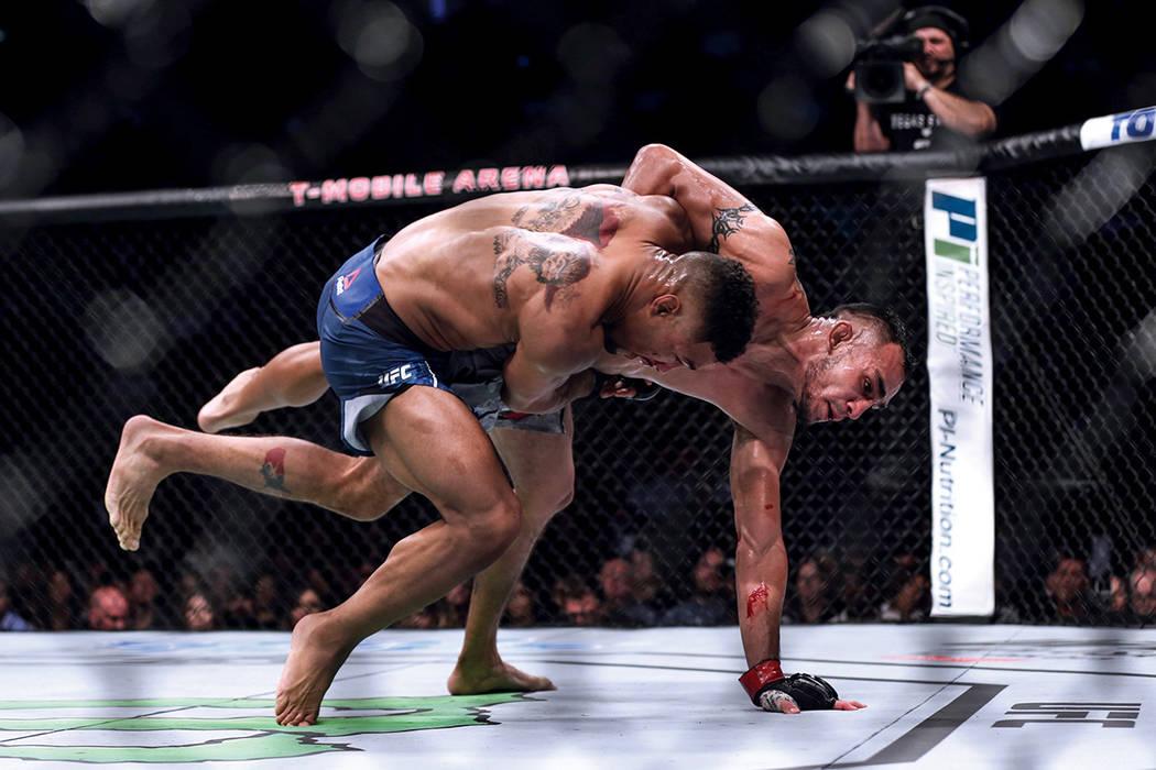 KevinLee, a la izquierda, derriba a Tony Ferguson, a la derecha, durante la pelea intermedia de campeonato de peso ligero UFC 216 en el T-Mobile Arena de Las Vegas. | Fotos Joel Ángel Juárez / L ...