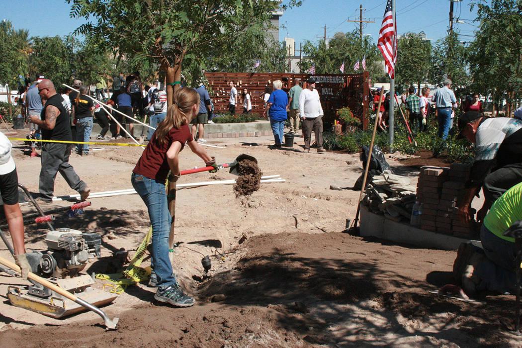 """Una jovencita voluntaria ayuda a construir el """"Jardín del alivio o sanación"""" de Las Vegas, dedicado a las 58 víctimas de la masacre del Strip. Al fondo se ven """"El árbol de la vida"""" y e ..."""
