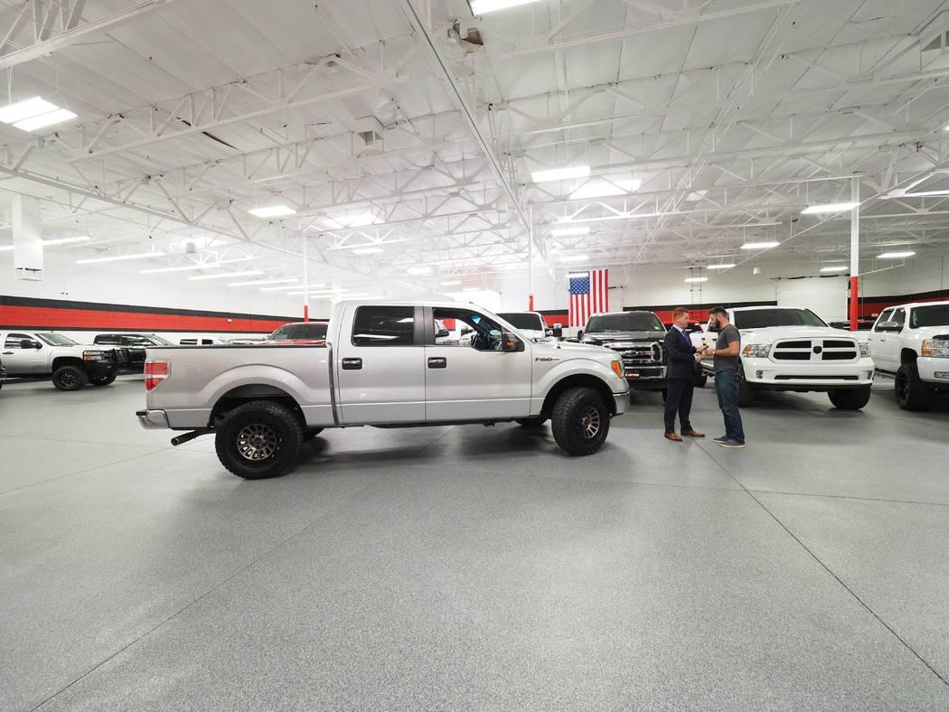 El propietario de B5 Motors Shane Beus en Gilbert, Arizona, presenta a Taylor Winston, de 29 años, con un camión F150 de 2013. el veterano de la marina estaba asistiendo al concierto del festiva ...