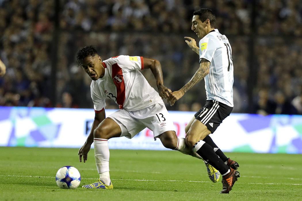 El peruano Renato Tapia, a la izquierda, lucha por el balón con el argentino Angel Di María durante un partido de fútbol clasificatorio para la Copa Mundial en el estadio La Bombonera de Buenos ...