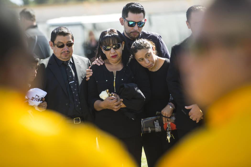 Gregorio De La Rosa, a la izquierda, y Angelica Cervantes, madre de Erick Silva, segunda desde la izquierda, durante los servicios funerarios de Silva en Davis Funeral Home & Memorial Park en  ...