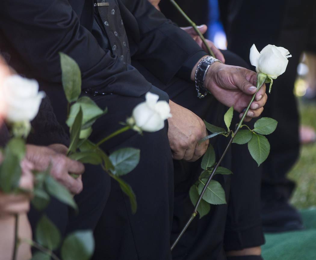 Gregorio De La Rosa, padrastro de Erick Silva, sostiene una rosa durante los servicios funerarios de Silva en Davis Funeral Home & Memorial Park en Las Vegas el jueves 12 de octubre de 2017. S ...