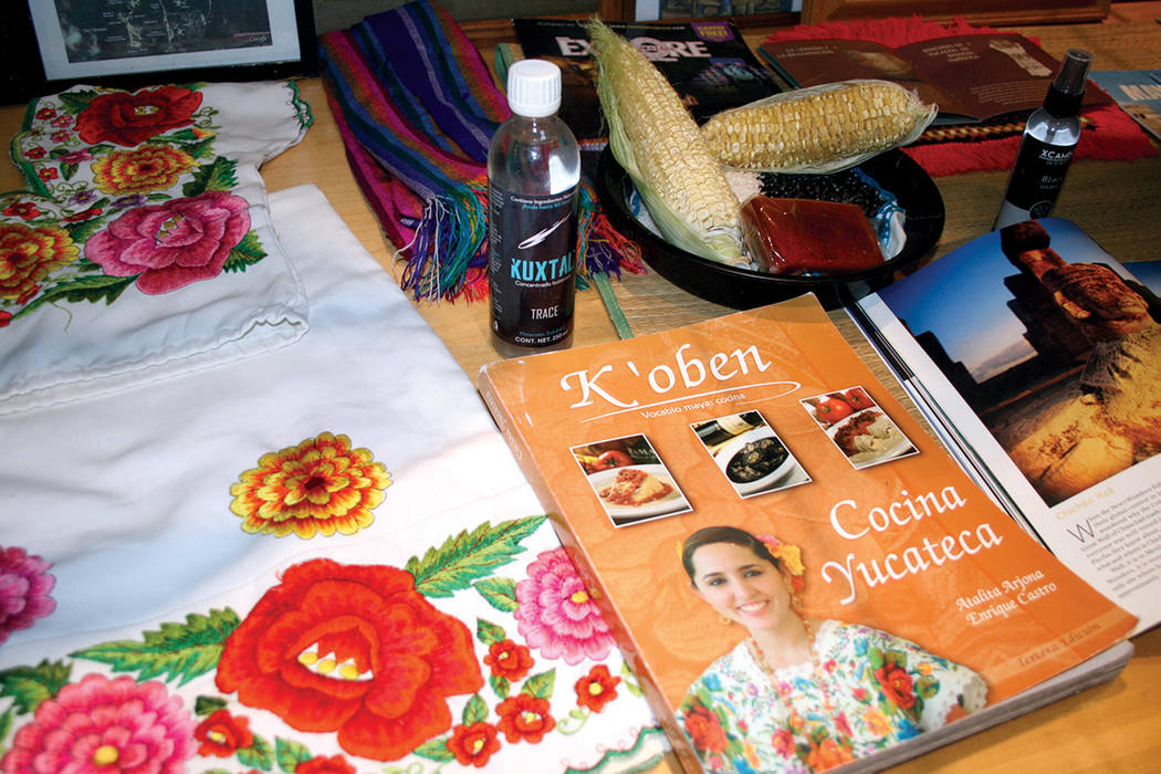 Aspecto de la Exhibición Mundo Maya Mágico muestra una vestimenta de mujer, unas mazorcas y un libro de la cocina yucateca, en la Biblioteca West Sahara. | Valdemar González / El Tiempo.