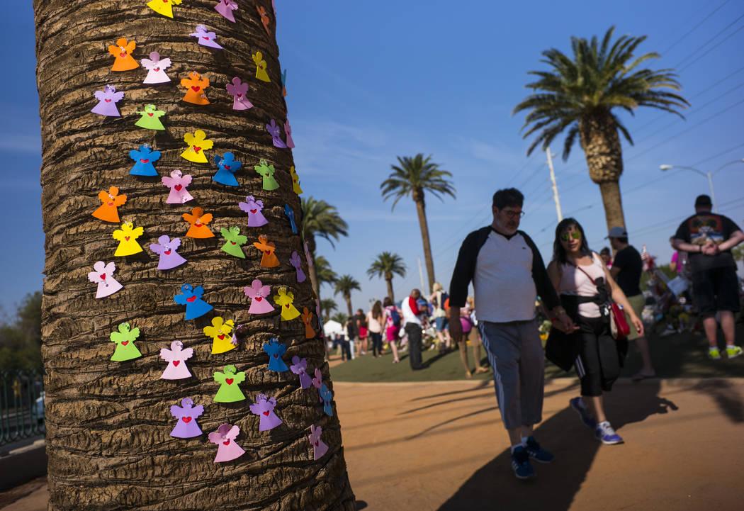 """Recortes que conmemoran a las 58 víctimas del tiroteo en masa son dejados en una palmera cuando la gente visita un monumento improvisado cerca del letrero de """"Bienvenido a Fabuloso Las Vegas"""" en  ..."""