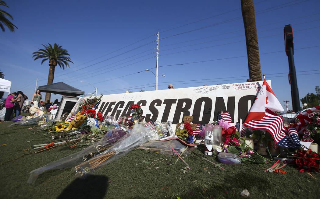 """La gente visita un monumento improvisado cerca del letrero """"Bienvenido a Fabuloso Las Vegas"""" en Las Vegas el viernes 13 de octubre de 2017. Chase Stevens Las Vegas Review-Journal @csstevensphoto"""