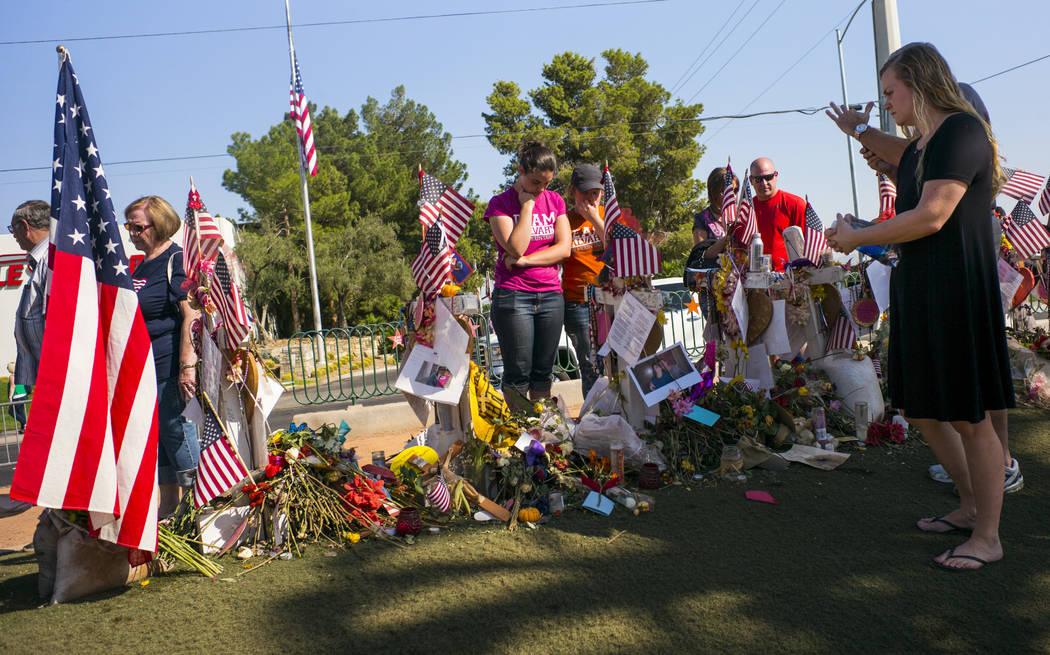 """La gente visita las cincuenta y ocho cruces dejadas en honor de las víctimas del tiroteo masivo en un monumento improvisado cerca del letrero de """"Bienvenido a Fabuloso Las Vegas"""" en Las Vegas el  ..."""