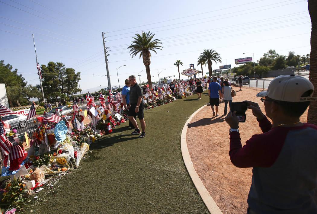 """La gente visita las cincuenta y ocho cruces dejadas en honor de las víctimas en el tiroteo masivo en un monumento improvisado cerca del letrero de """"Bienvenido a Fabuloso Las Vegas"""" en Las Vegas e ..."""