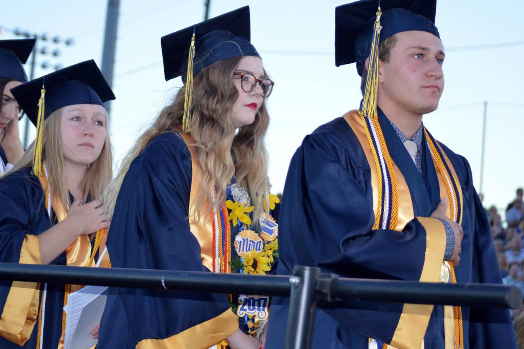 Salutatorian Alea Lehr, izquierda y valedictorians Mira Newby center, y Michael Martinelli escuchan el himno nacional durante la ceremonia de graduación de la Escuela Secundaria de Boulder City e ...