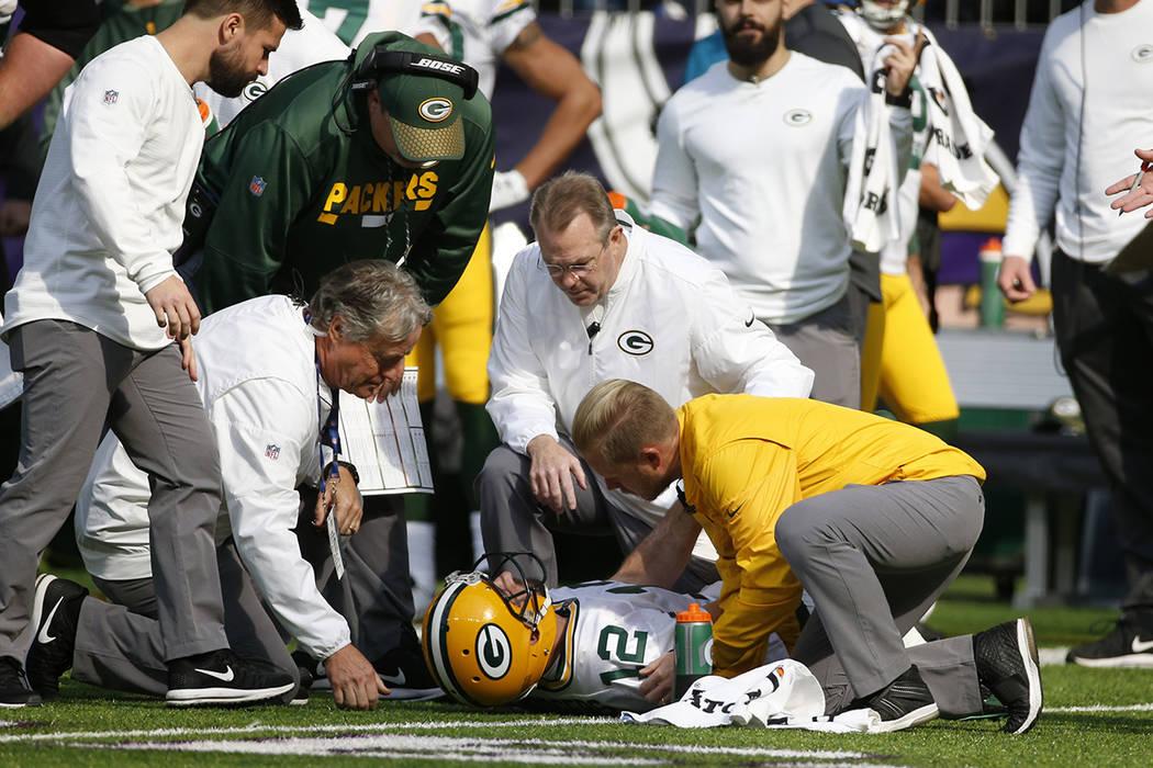 El mariscal de campo de Green Bay Packers Aaron Rodgers (12) es atendido por personal médico después de ser golpeado por el apoyador externo de Minnesota Vikings Anthony Barr (55) en la primera  ...