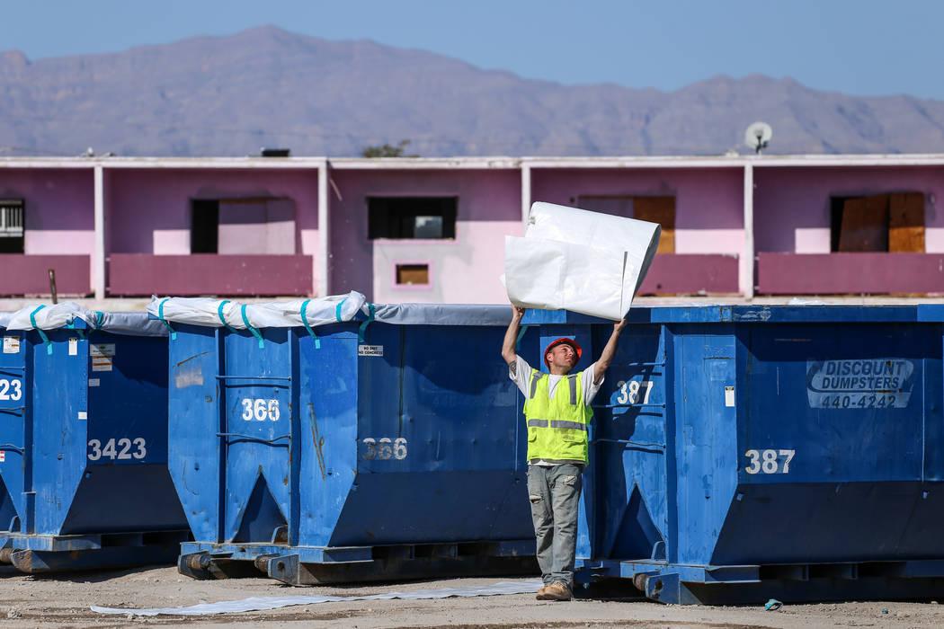Un trabajador arroja un revestimiento de plástico sobre un contenedor de basura mientras los equipos limpian los restos del demolido Moulin Rouge en Las Vegas, el jueves 19 de octubre de 2017. Jo ...