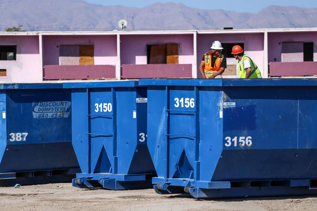 Los trabajadores se sientan en los contenedores de basura mientras las tripulaciones limpian los restos del demolido Moulin Rouge en Las Vegas, el jueves 19 de octubre de 2017. Joel Angel Juarez L ...