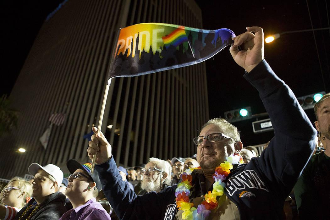 """El asistente Ken Wells sostiene una bandera que dice """"Orgullo"""" mientras una drag queen se presenta durante el 19no Desfile Nocturno anual de PRIDE en el centro de Las Vegas, viernes, 20 de octubre ..."""