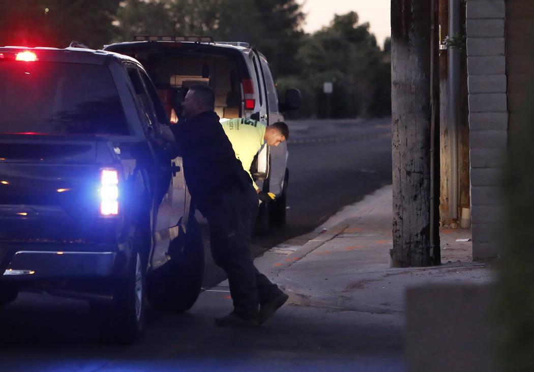Un trabajador remueve manchas de sangre de la acera donde la policía de Las Vegas investiga el choque de una motocicleta robada en la calle Topaz, cerca de la avenida Tropicana, el martes 24 de o ...