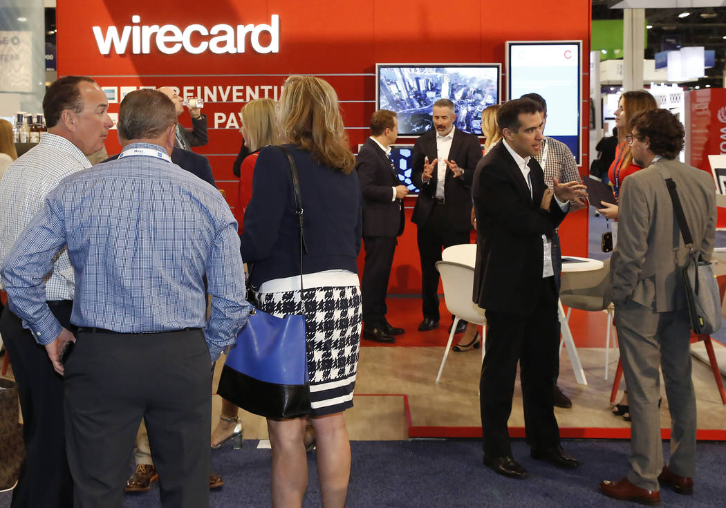 Los asistentes se reúnen en el stand de Wirecard durante la conferencia Money 20/20 2017 en el Sands Expo and Convention Center el lunes 23 de octubre de 2017 en Las Vegas. (Bizuayehu Tesfaye / L ...