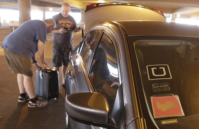 Los pasajeros se preparan para cargar su equipaje en el automóvil Uber y Lyft de las compañías de Ride-hailing en el Aeropuerto Internacional McCarran en la Terminal 1 el jueves 20 de octubre d ...