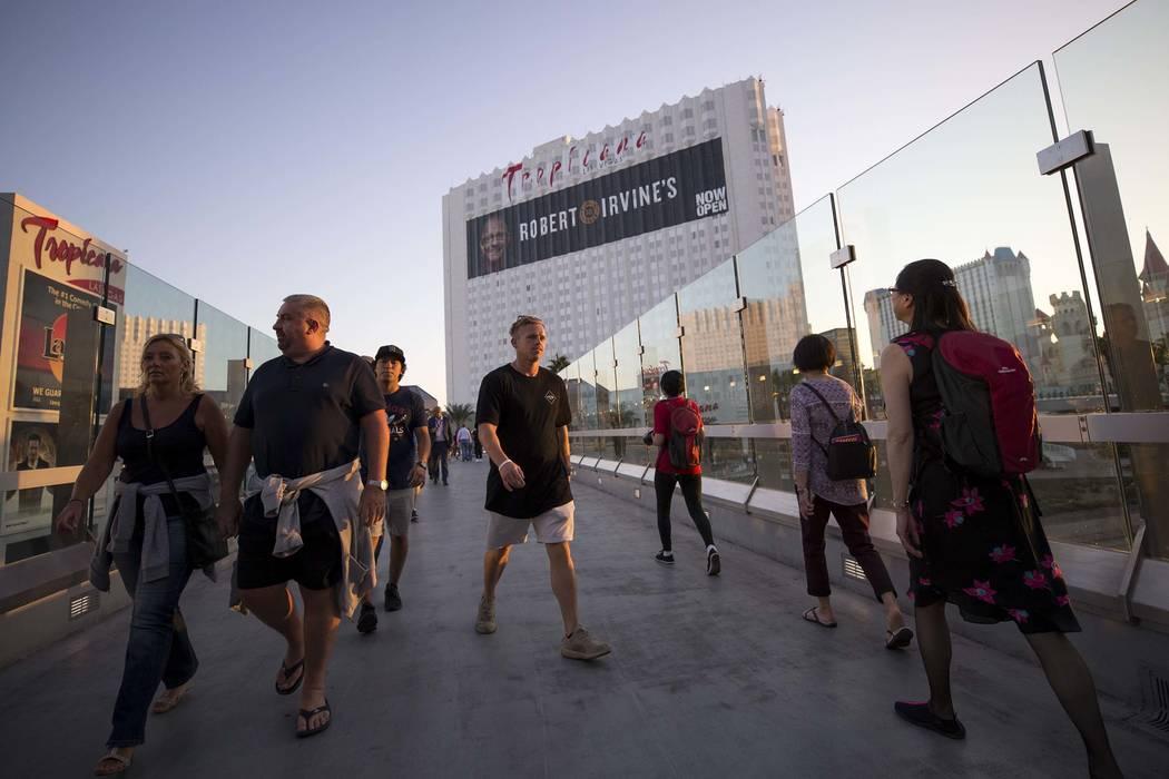 La gente camina sobre un puente peatonal que une a MGM Grand y Tropicana hotel-casino, cerca de la intersección de Las Vegas Boulevard y Tropicana Avenue en Las Vegas, el jueves 12 de octubre de  ...