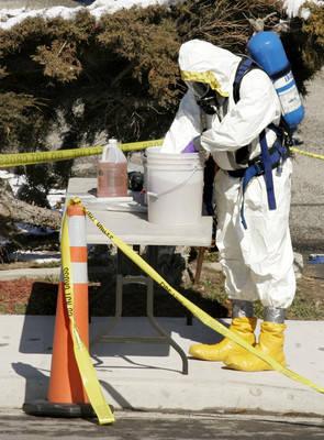 Una persona vestida con un atuendo HAZMAT para sustancias peligrosas trabaja fuera de una casa el domingo 2 de marzo de 2008 en Riverton, Utah. Los agentes del FBI registraron la casa y dos unidad ...