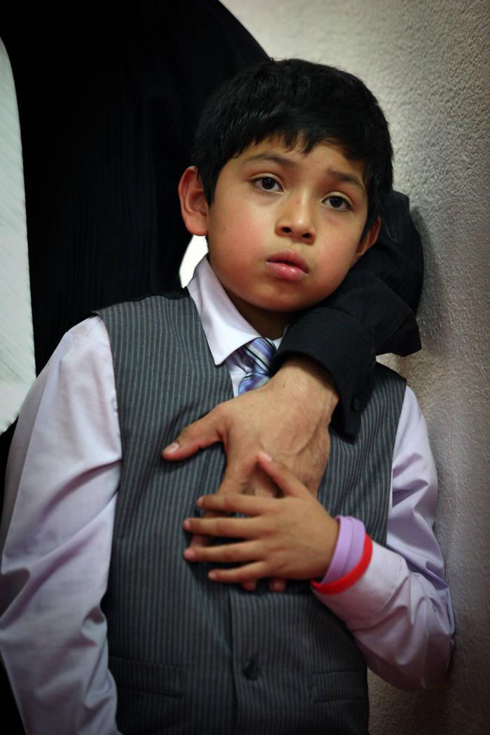 Christopher Martínez, de 9 años, toca la mano de su padre Arturo Martínez el 12 de julio de 2012, en el Real KO Boxing Gym en North Las Vegas. Arturo Martínez casi fue golpeado hasta la muerte ...