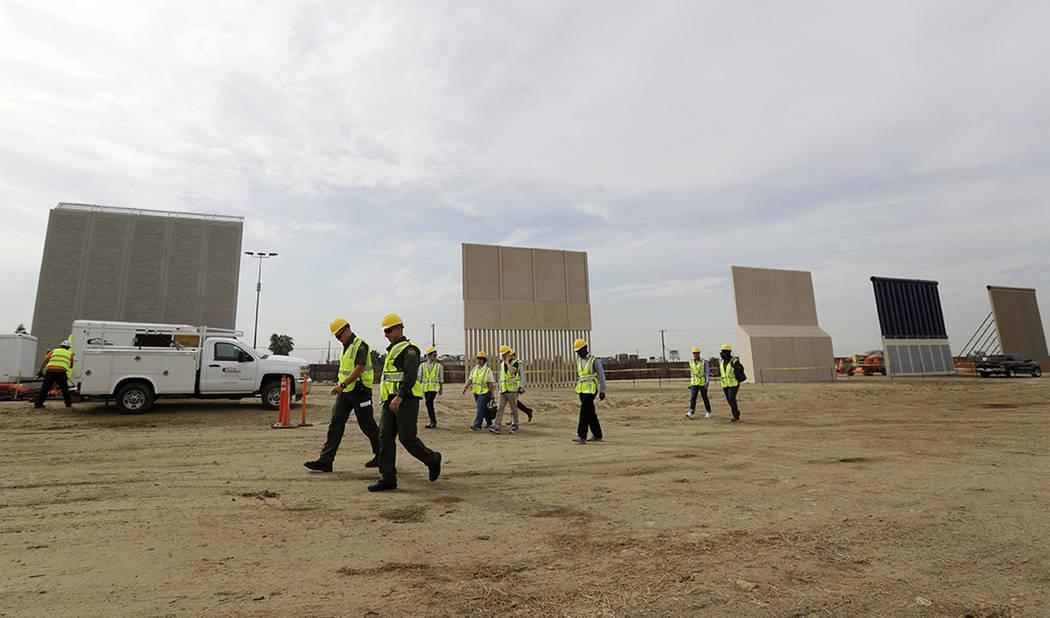 Las personas pasan prototipos de paredes fronterizas cuando se encuentran cerca de la frontera con Tijuana, México, el jueves 19 de octubre de 2017 en San Diego. Las empresas se acercan a la fech ...