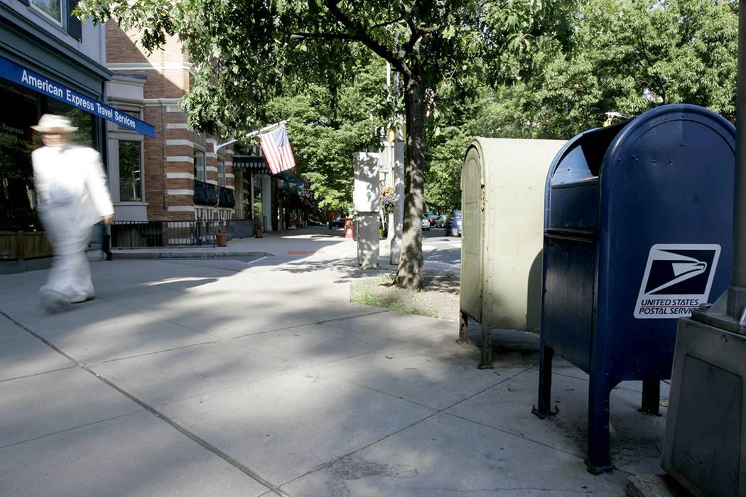 ARCHIVO- PARA ILUSTRAR- Un hombre camina junto a un buzón del Servicio Postal de los Estados Unidos, a la derecha, frente a 10 Nassau Street en Princeton, NJ, el lunes 4 de agosto de 2008. | Foto ...