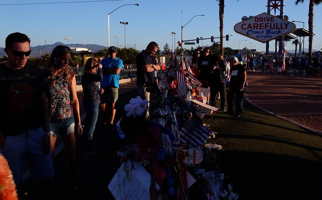 """Matt, a la izquierda y Robyn Webb presentan sus respetos en un monumento improvisado para las víctimas del 1° de octubre en el letrero """"Bienvenido a Fabuloso Las Vegas"""" en Las Vegas el jueves 26 ..."""