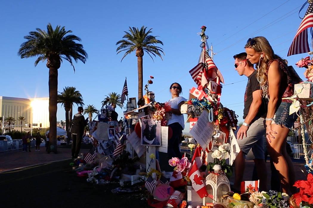 """Robyn Webb, a la derecha, y su esposo Matt Webb presentan sus respetos en un monumento improvisado para las víctimas del 1° de octubre en el letrero """"Bienvenido a Fabuloso Las Vegas """" en Las Veg ..."""