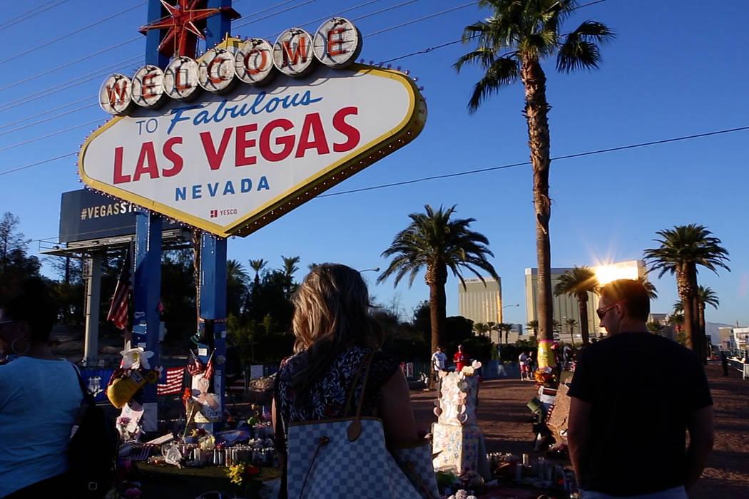 """Robyn Webb, a la izquierda, y su esposo Matt Webb llegan a presentar sus respetos en un monumento improvisado para las víctimas del 1° de octubre en el letrero """"Bienvenido a Fabuloso Las Vegas """" ..."""