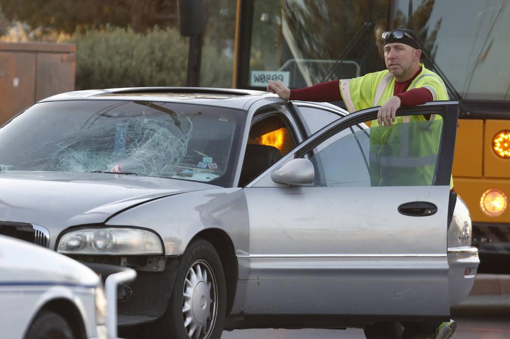 Un conductor de una grúa se para junto a un automóvil involucrado en un accidente en Commerce Street a la altura de Rossmoyne Avenue en North Las Vegas el jueves, 2 de noviembre de 2017. Un adol ...