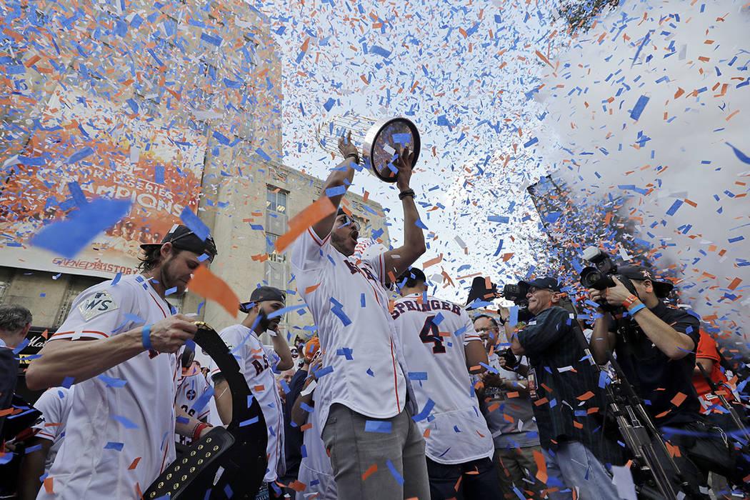 Carlos Correa de los Astros de Houston levanta el trofeo del campeonato mientras celebra con sus compañeros durante un mitin en honor a los campeones de la Serie Mundial de béisbol el viernes 3  ...