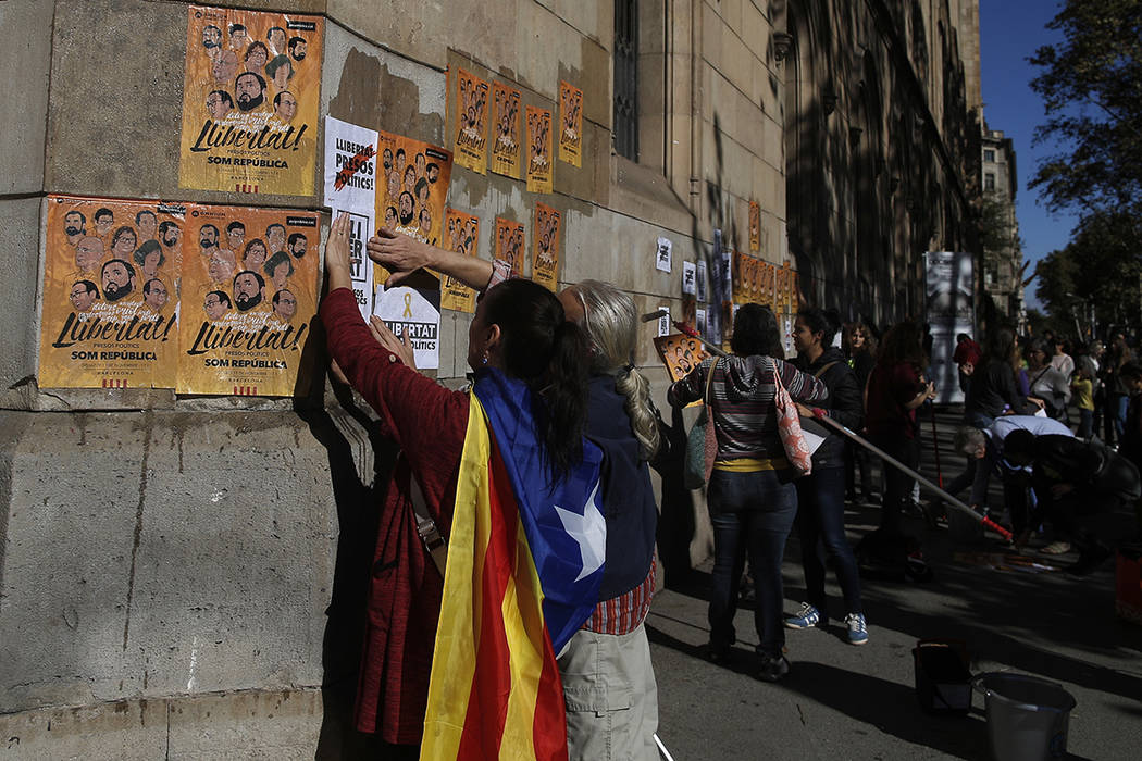 """Una mujer con una 'Estelada', la bandera catalana proindependentista colgada sobre su hombro, pega pancartas en una pared que dice en catalán: """"Libertad para los presos políticos"""" durante una pr ..."""