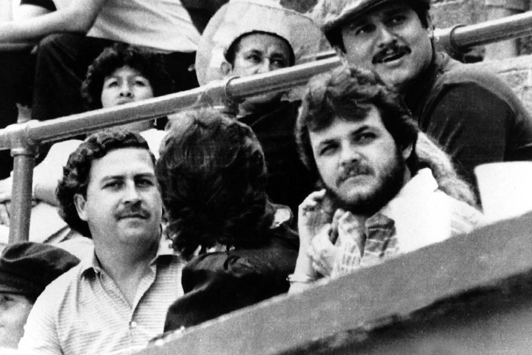 ARCHIVO - En esta foto de archivo de 1983, el jefe del cartel de Medellín, Pablo Escobar, a la izquierda, ve un partido de fútbol en Medellín, Colombia. Una película documental que explora la  ...