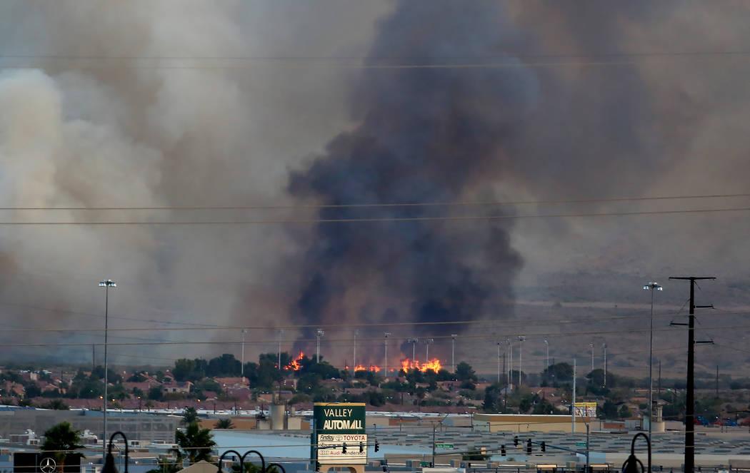 El humo y las llamas son visibles en el Clark County Wetlands Park, cerca del estadio Sam Boyd, el lunes 6 de noviembre de 2017 en Las Vegas. El fuego abarca alrededor de 3-5 hectáreas en una par ...