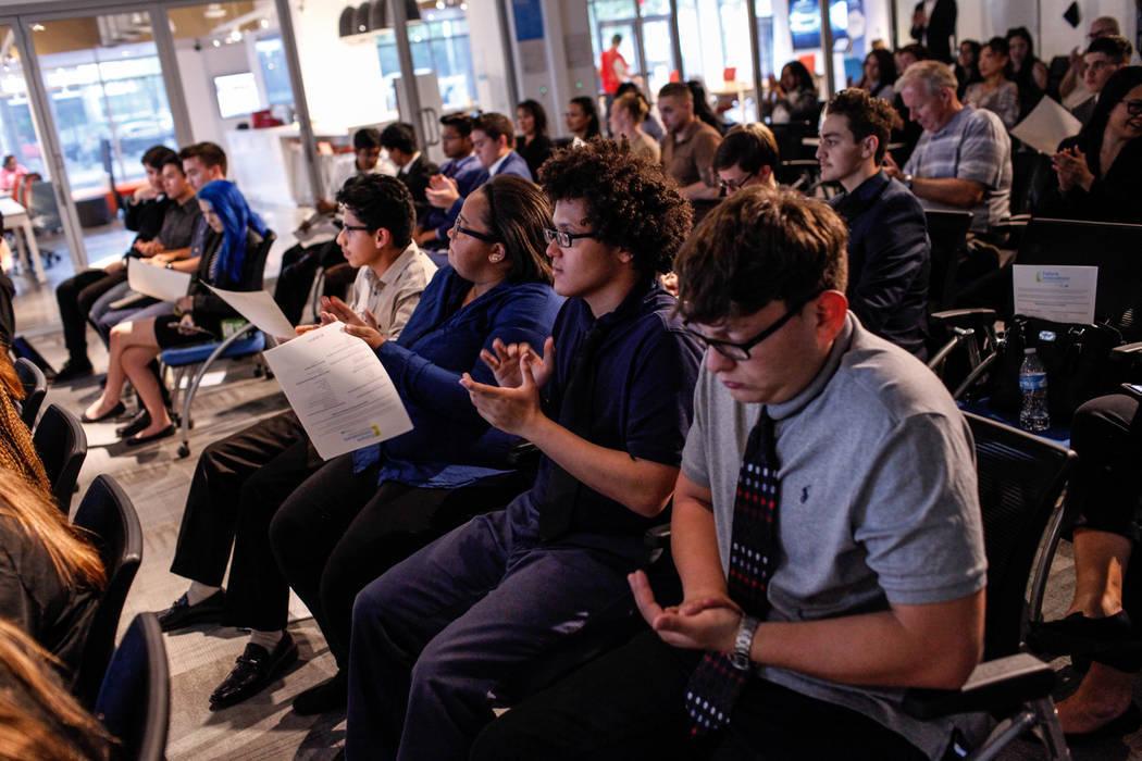 Los estudiantes de Basic High School Filipe Deandrade, de 18, segundo de la derecha, y Joshua Gutierrez, de 16, a la derecha, aplauden durante la Competencia de lanzamiento de negocios de CTA Futu ...