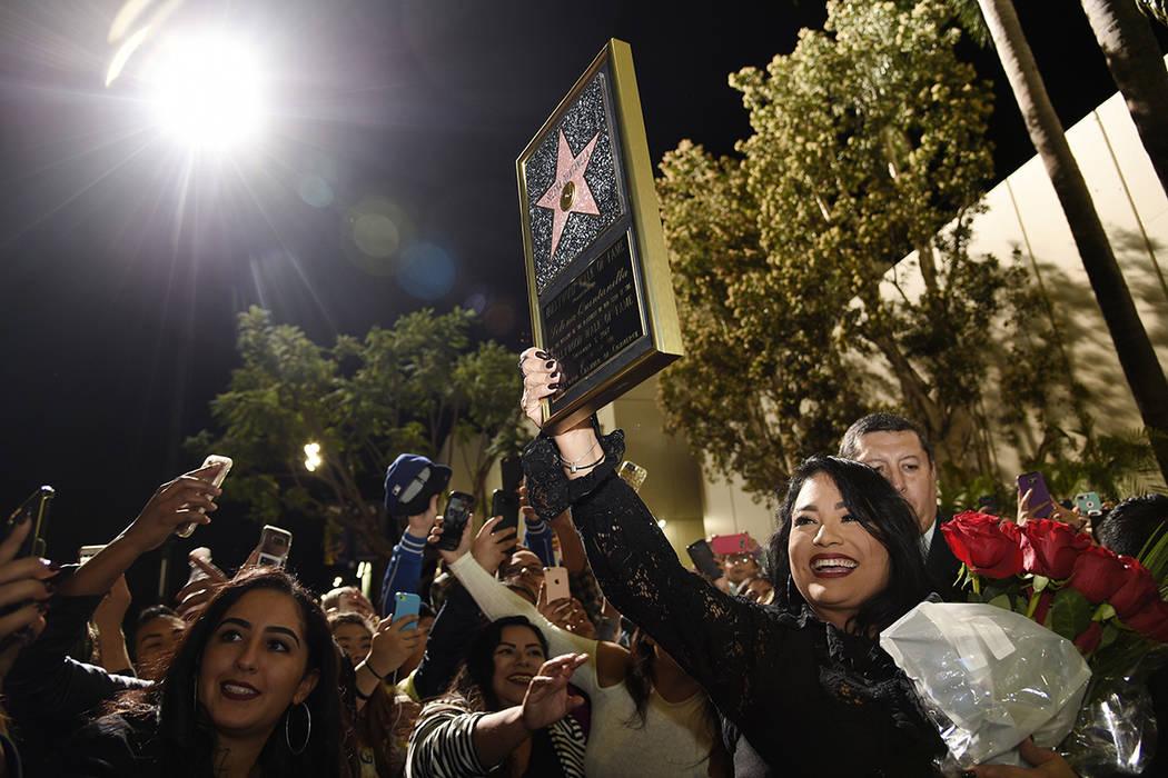 Suzette Quintanilla, hermana de la fallecida cantante Selena Quintanilla, muestra una réplica de la estrella de su hermana en el Paseo de la Fama de Hollywood a la multitud después de una ceremo ...