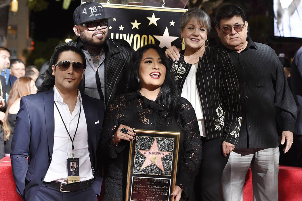 Suzette Quintanilla, del centro, hermana de la fallecida cantante Selena Quintanilla, sostiene una réplica de su nueva estrella en el Paseo de la Fama de Hollywood mientras posa con, desde la izq ...