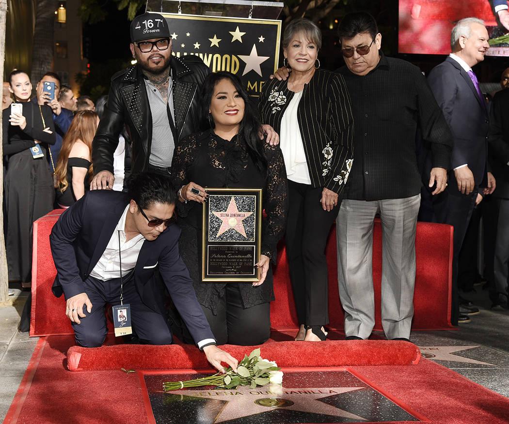 Chris Perez, abajo a la izquierda, el ex esposo de la fallecida cantante Selena Quintanilla, le pone flores a su nueva estrella en el Paseo de la Fama de Hollywood mientras posa con, de izquierda  ...