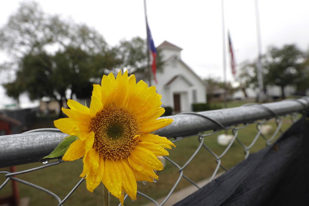 La lluvia se acumula en una flor que queda en la valla afuera de la Iglesia Bautista Sutherland Springs para ver un memorial, el domingo 12 de noviembre de 2017, en Sutherland Springs, Texas. Un h ...