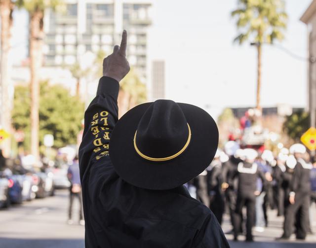 Un miembro de los Buffalo Soldiers señala un avión de combate F-35 haciendo un sobrevuelo durante el Desfile del Día de los Veteranos en el centro de Las Vegas el viernes 11 de noviembre de 201 ...