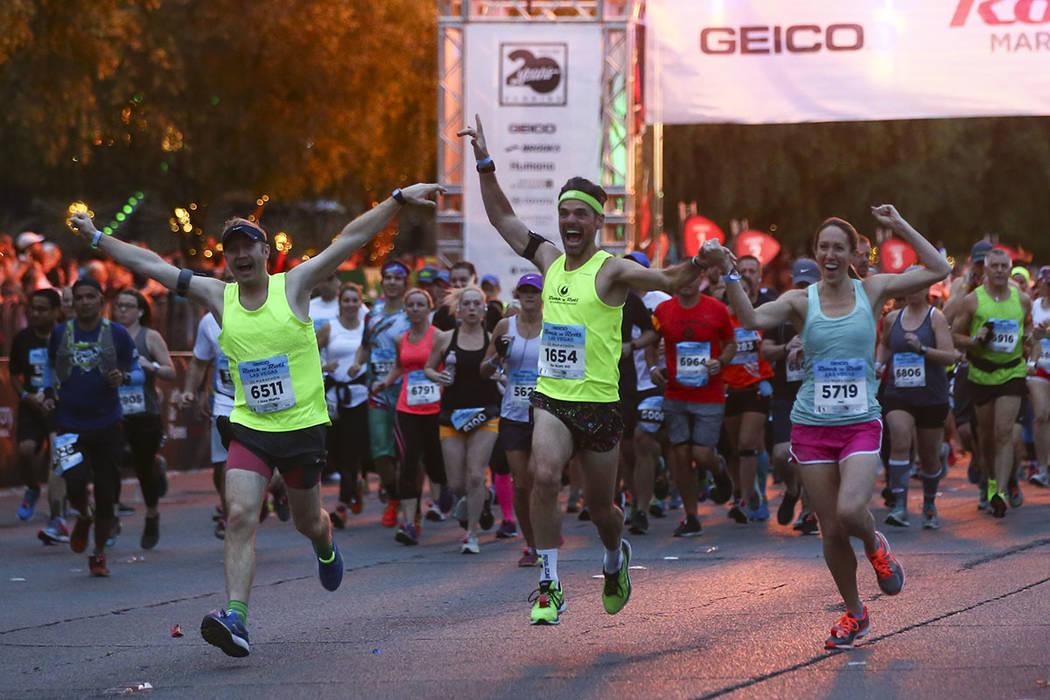 Los participantes (de izquierda a derecha) Peter Smith, Scott Desbois y Jen Desbois salen de la línea de salida a las afueras del casino New York-New York al comienzo del maratón de Rock 'n' ...