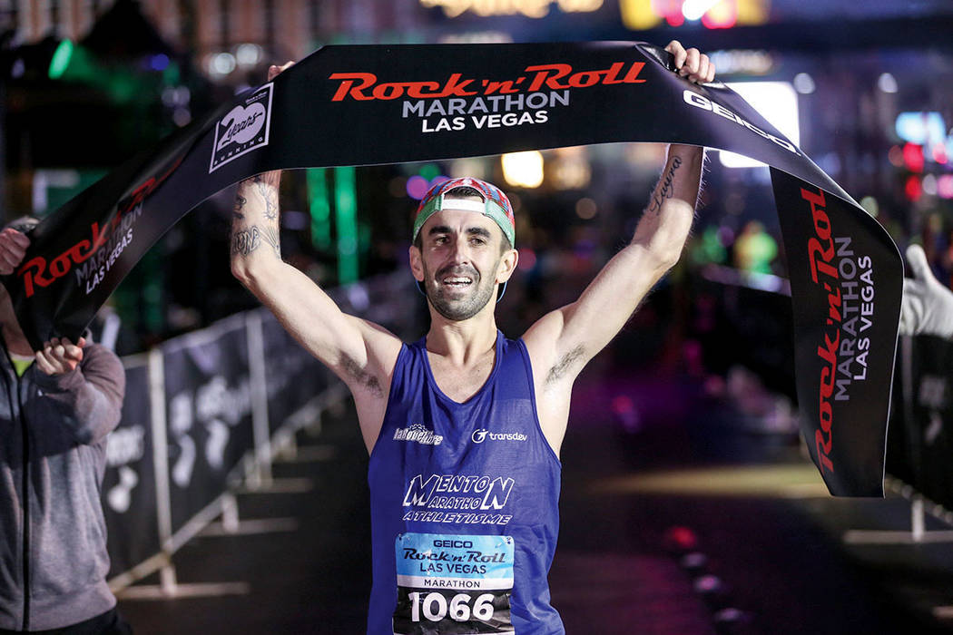 Gilles Rubio de Roquebrune Cap Martin, Francia, cruza la línea de meta ganando el primer puesto en la categoría varonil del Maratón de Rock 'n' Roll Las Vegas realizado en el Strip, cerca d ...
