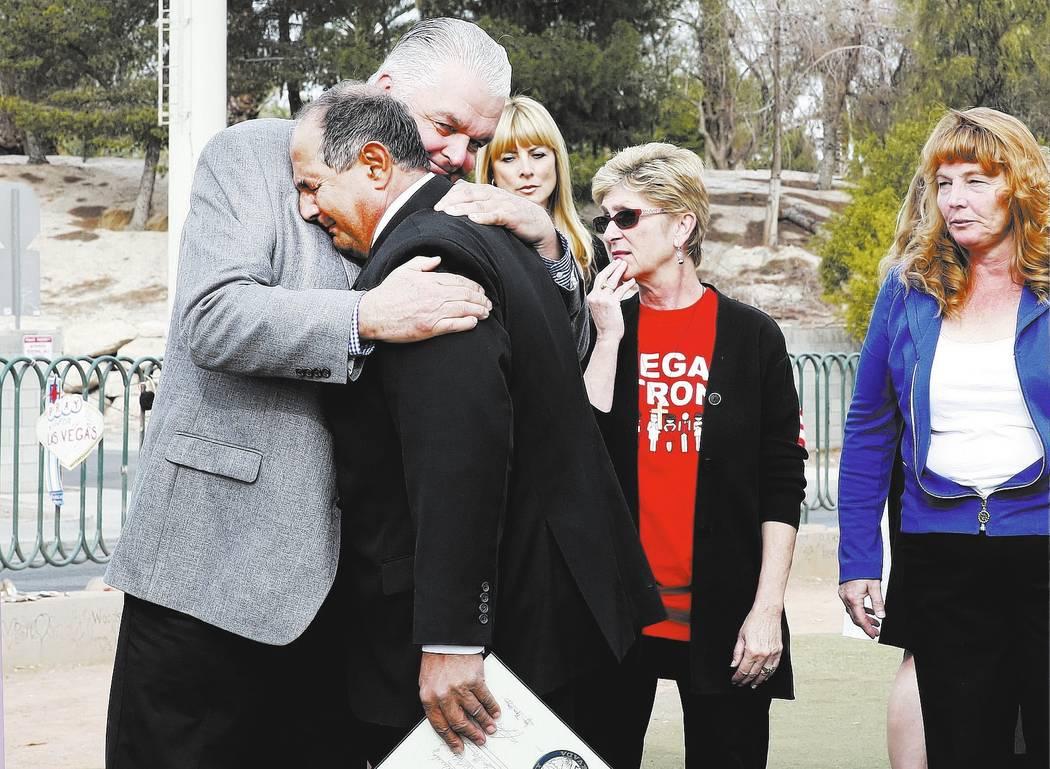 """El Comisionado del Condado de Clark Steve Sisolak, a la izquierda, da un abrazo a Greg Zanis después de declarar el domingo """"Greg Zanis Day"""" en el Memorial de la Ruta 91 Harvest en el letrero Wel ..."""