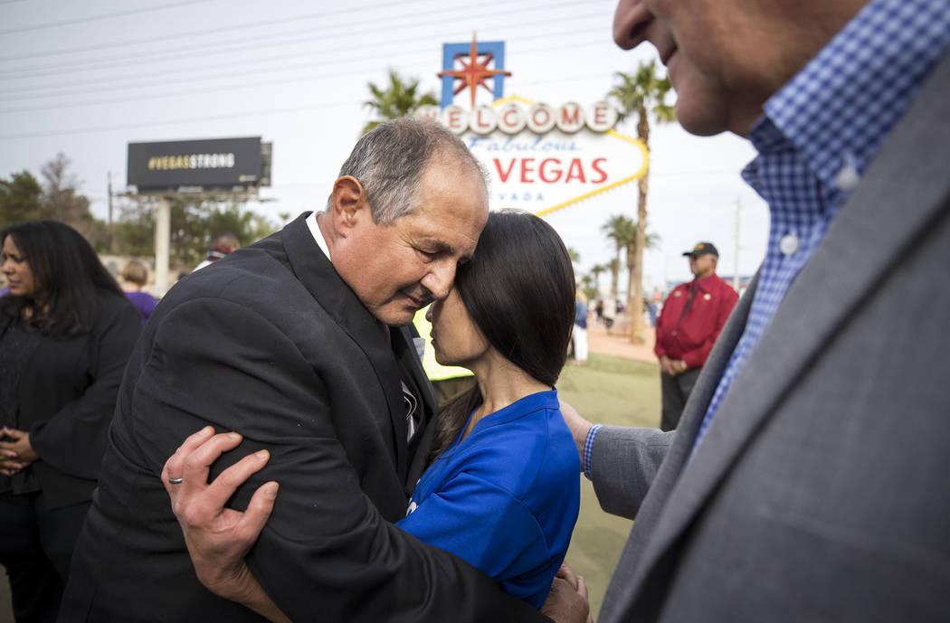 Tracy Shipp, al centro, hermana de la víctima de la Ruta 91 Laura Shipp, es consolada por Greg Zanis, izquierda, y Steve Sisolak, presidente de la Comisión del Condado de Clark, después de una  ...
