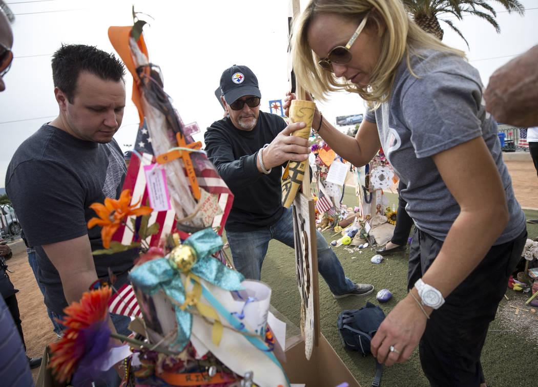 Chris Davis, al centro, y Mynda Smith, a la derecha, padre y hermana de la víctima de tiroteo de la Ruta 91 Neysa Tonks, recogen objetos de la cruz de Tonks durante una conmovedora ceremonia en u ...