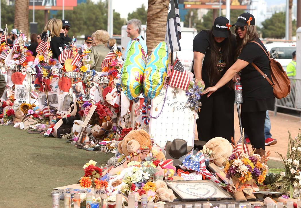 Las sobrevivientes del tiroteo en Las Vegas, incluida Lulu Farina, a la derecha, visitan el monumento conmemorativo de la Ruta 91 en el cartel de Bienvenido a fabuloso Las Vegas  el domingo 12 de  ...
