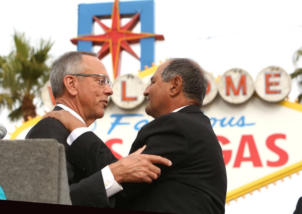 Jim Gibson, comisionado del Condado de Clark, a la izquierda, habla con Greg Zanis después de declarar el domingo Sunday ҇reg Zanis DayӠ en el monumento conmemorativo de la Ruta 91 en el cartel ...