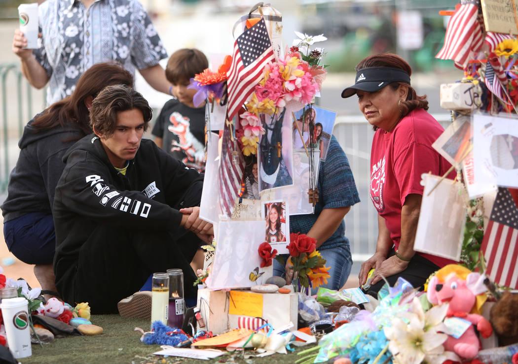 Matthew Ferandell, a la izquierda, visita la cruz de su prima Angela Gomez en el Memorial de la Cosecha Route 91 en el cartel de Welcome to Fabulous Las Vegas el domingo, 12 de noviembre de 2017,  ...