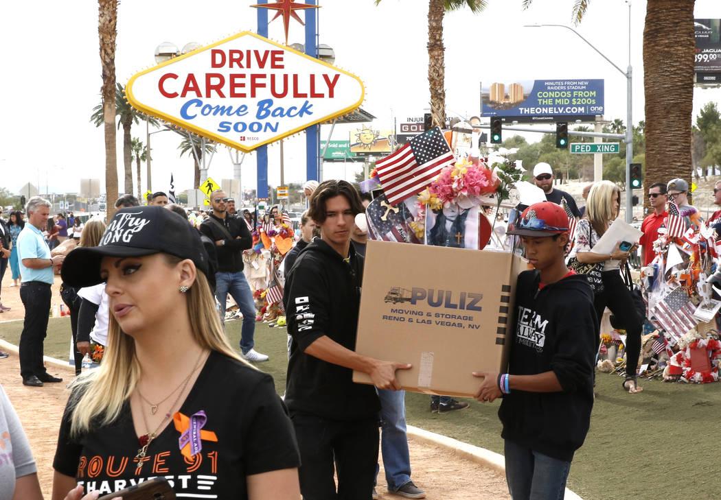 Matthew Ferandell, al centro, primo de Angela Gomez, víctima del tiroteo el 1 de octubre, y Ben Riccardi, a la derecha, llevan la cruz empacada y artículos del Memorial de la Cosecha Route 91 en ...