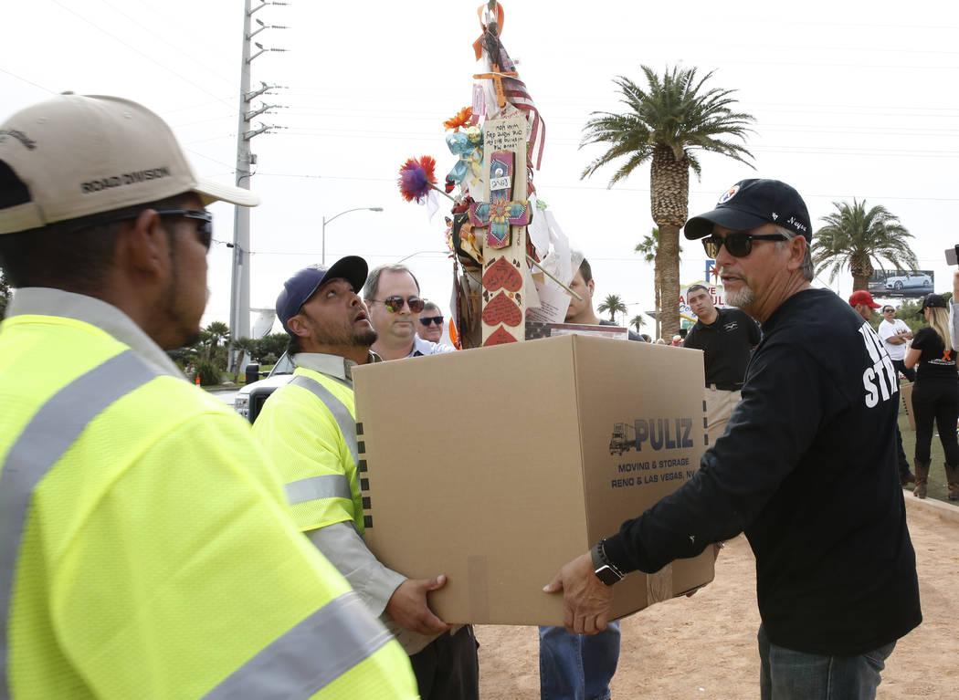 Chris Davis, a la derecha, ayuda a los empleados del Condado de Clark que portan su cruz Neysa Tonks, su hija víctima de disparos en Las Vegas, y objetos en el letrero Bienvenido a  fabuloso Las  ...
