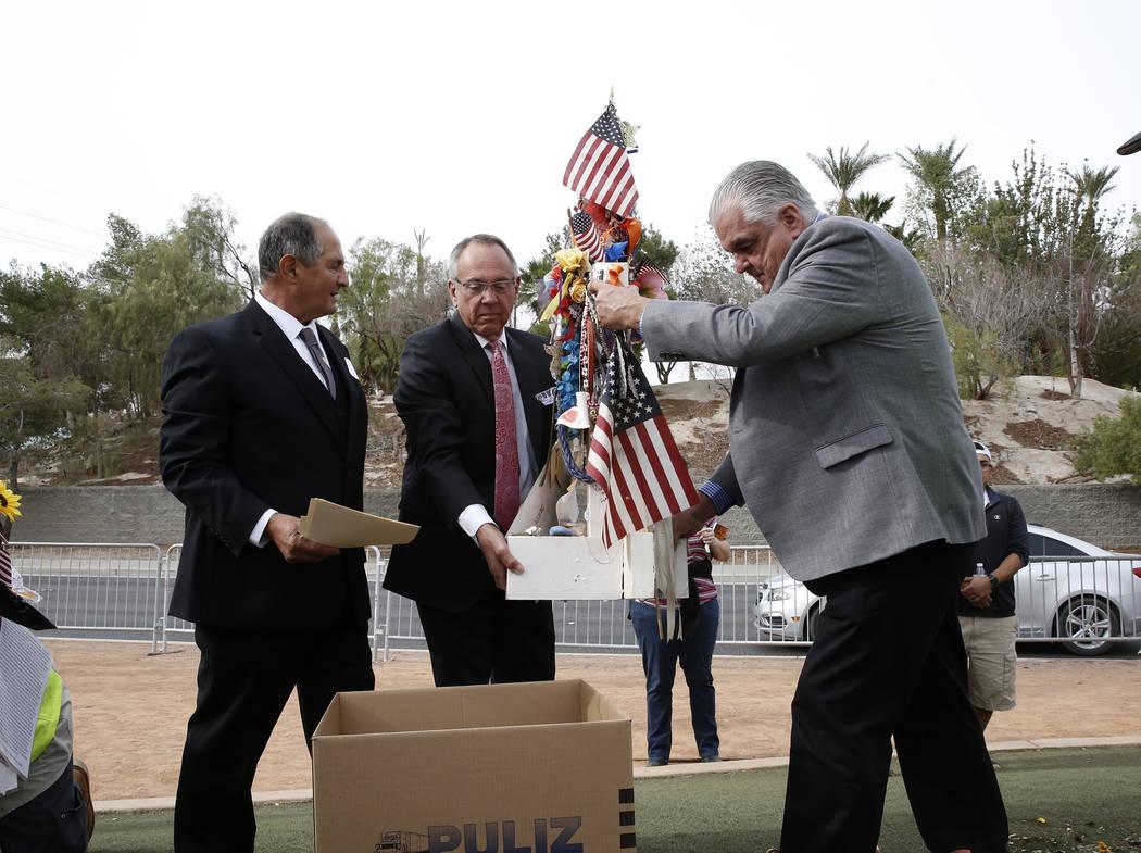 Los comisionados del Condado de Clark, Jim Gibson, en el centro, y Steve Sisolak, a la derecha, ayudan a retirar las cruces del Memorial de la Cosecha de la Ruta 91 en el cartel de Bienvenido a  F ...