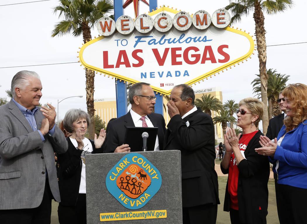 """Greg Zanis, al centro, se emociona después de que el Comisionado del Condado de Clark Jim Gibson, segundo a la izquierda, declara el domingo ҇""""Greg Zanis Day"""" en el monumento conmemorativo de la ..."""